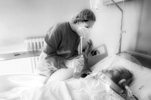 """La fotografia ritrae un operatore sanitario conforta un malato di covid attaccato ad un respiratore, da """"COVID19: quei giorni, sotto il cielo di Urbino di Tonino Mosconi"""